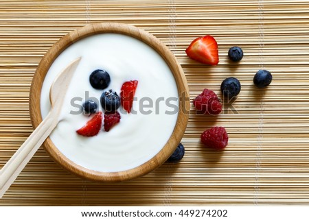 Wooden bowl of white yogurt with wooden spoon inside on bamboo matt from above. Next to berries.