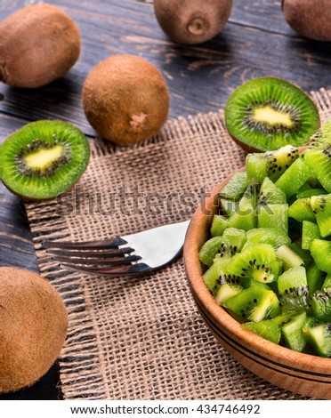 Wooden bowl with a salad of kiwi fruit and a fork on the table - stock photo