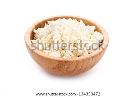 wooden bowl with cottage cheese over white background - stock photo