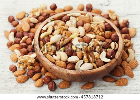 Wooden bowl with mixed nuts on white table. Healthy food and snack. Walnut, pistachios, almonds, hazelnuts and cashews. - stock photo