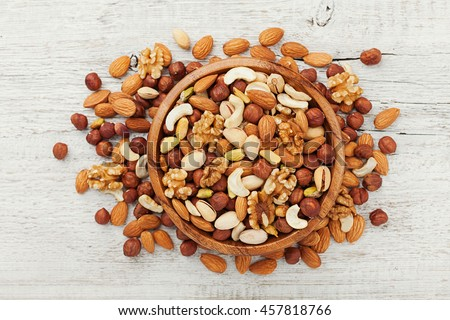 Wooden bowl with mixed nuts on white table top view. Healthy food and snack. Walnut, pistachios, almonds, hazelnuts and cashews.