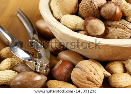 Wooden bowl with nuts - hazelnuts, almonds, walnuts, peanuts, pecan nuts and nutcarker.