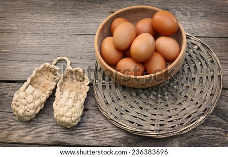 Wooden bowl with the brown eggs  and bast on the table