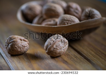 wooden bowl with walnuts on rustic table