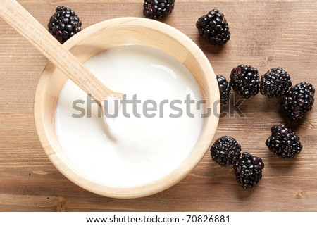 Wooden bowl with Yogurt and blackberries - stock photo