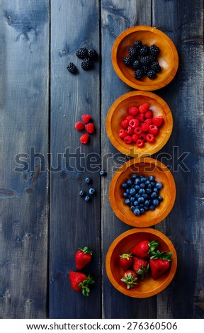 Wooden bowls with organic berries (strawberries, raspberries, blueberries and blackberries) on dark texture. Background with space for text. Agriculture, Gardening, Harvest Concept - stock photo
