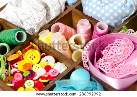 Wooden box with accessories for sewing and embroidery - stock photo