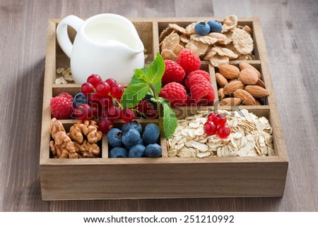wooden box with breakfast items - oatmeal, granola, nuts, berries and milk on table - stock photo