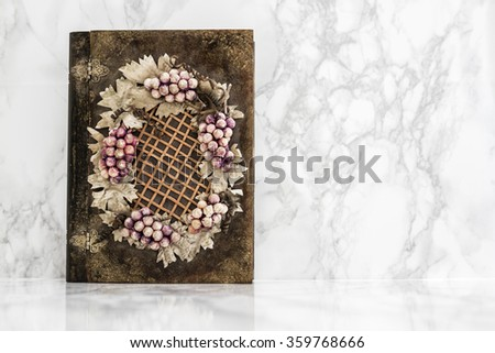 Wooden box with grapes and leaves figures on white marble table