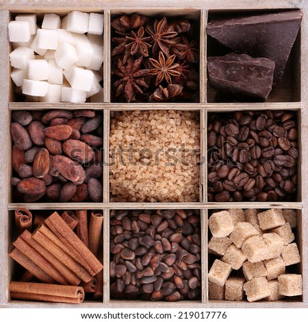 Wooden box with set of coffee and cocoa beans, sugar cubes, dark chocolate, cinnamon and anise over wooden background - stock photo