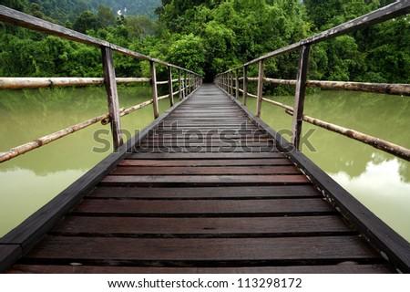 Wooden bridge across in the lake - stock photo