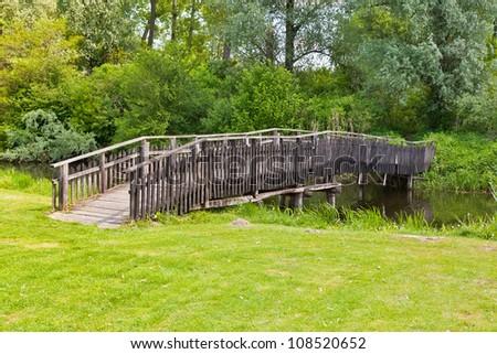 Wooden bridge across the pond in the woods - stock photo