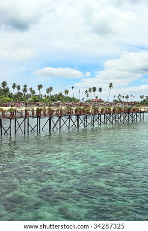 Wooden bridge built above water at Mabul Island. - stock photo