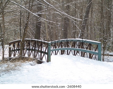 wooden bridge covered with snow - stock photo