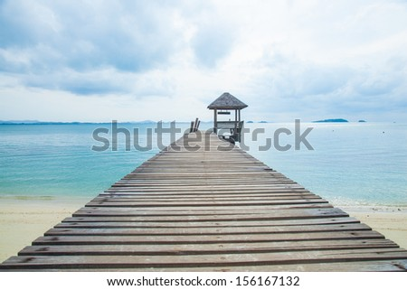 Wooden bridge into the sea. Property is located at the end of the runway into the sea. - stock photo