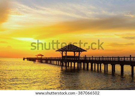Wooden bridge jutting out into the sea and sunset.