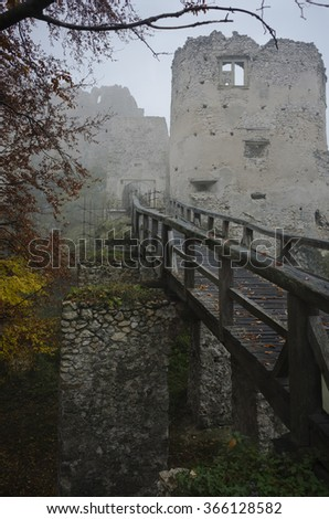 wooden bridge leading to an old mystical castle ruin in fog,mist