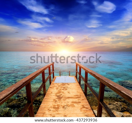 wooden bridge on sea against sunset background