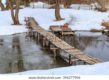 Wooden bridge over a small river, winter day
