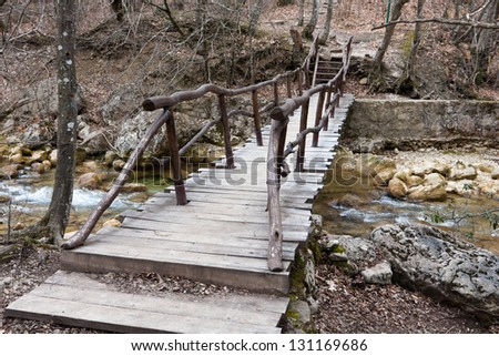 wooden bridge over mountain brook - stock photo