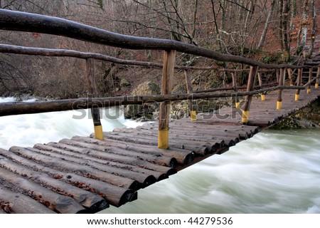 Wooden bridge over mountain stream - stock photo