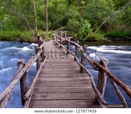 Wooden bridge over swift river. - stock photo