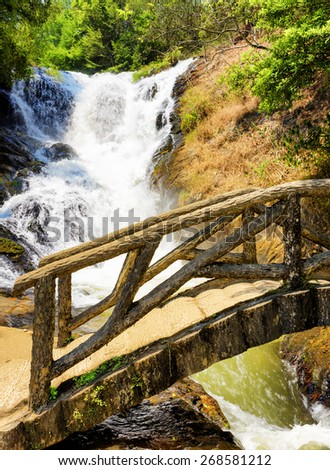 Wooden bridge over the gorge and the Datanla waterfall in Da Lat city (Dalat), Vietnam. Da Lat and the surrounding area is a popular tourist destination of Asia. - stock photo
