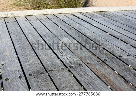 wooden bridge planks going on to the beach - stock photo