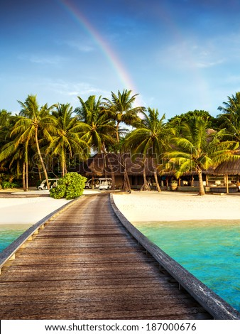 Wooden bridge to island beach resort, beautiful colorful rainbow over fresh green palm trees, luxury hotel on Maldives island, summer vacation concept - stock photo