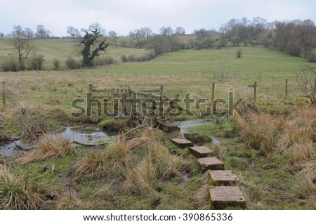 Wooden Bridge with a Gate and Stile over Bletch Brook, near the Rural Village of Tissington, within the Peak District National Park, Devon, England, UK - stock photo