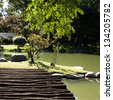 wooden bridge with and pond in the park - stock photo