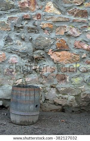 Wooden brown barrel on a stone wall