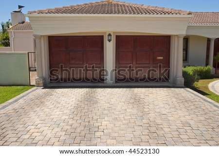Wooden brown double garage doors of a big house with the drive way in the foreground - stock photo