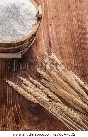 wooden bucket with ears of wheat on vintage board