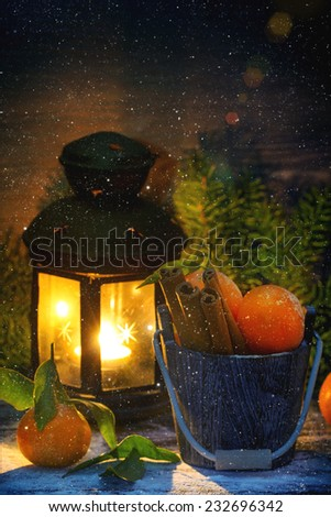 Wooden bucket with tangerines and cinnamon sticks over wooden background with burning lantern, falling snow and Christmas tree. - stock photo