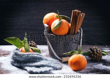 Wooden bucket with tangerines and cinnamon sticks over wooden background with snow and cone. - stock photo