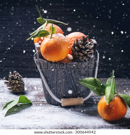 Wooden bucket with tangerines over wooden background with snow and cone. Square image with selective focus - stock photo