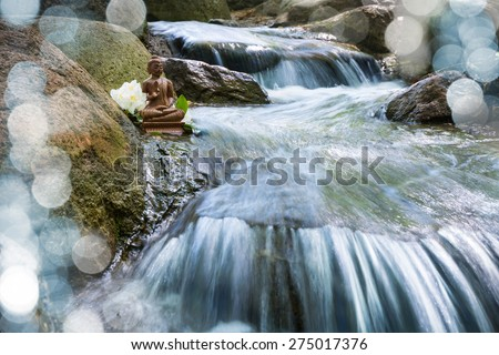 Wooden Buddha statue on a creek - stock photo