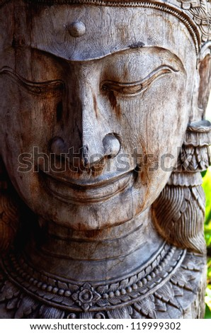 Wooden Buddha Statue with Cropped  Head and in Heavy Light and Shadow. Buddhism icon. - stock photo