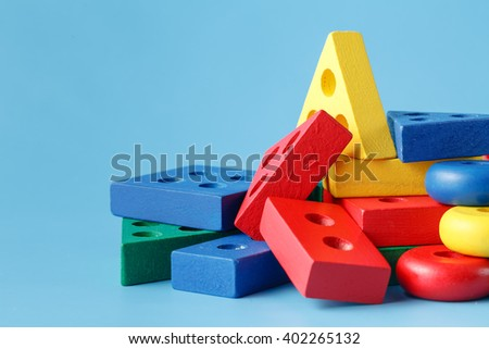 Wooden building blocks on blue - stock photo