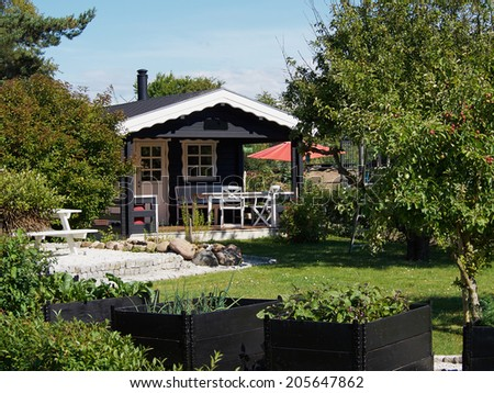Wooden bungalow cabin painted black in a beautiful garden - stock photo