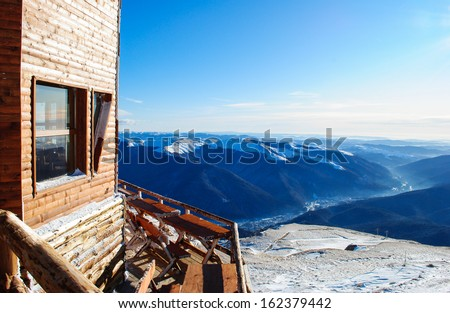 wooden cabin facing the snowy peaks of mountains in the cold winter - stock photo