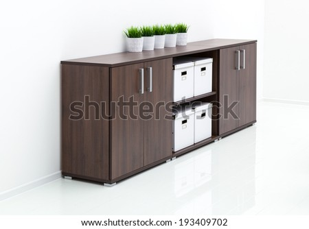 wooden cabinet against a white wall - stock photo