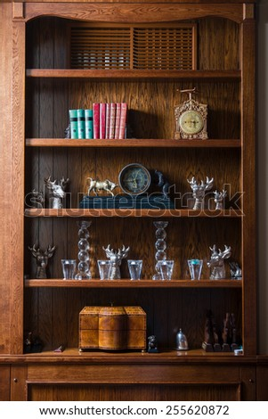 Wooden cabinet in the living room with the clock, glasses, books, candles and boxes. - stock photo