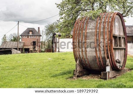 Wooden Calvados barrels with iron rings, with peasant's house on the background in Cambremer, Normandy, Franc - stock photo
