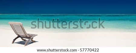 wooden canvas chair on a beautiful tropical beach - stock photo