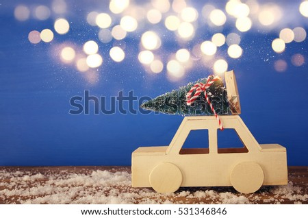 Wooden car carrying a christmas tree on the table. Glitter overlay