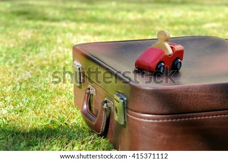 wooden car on suitcase put in the grass - stock photo