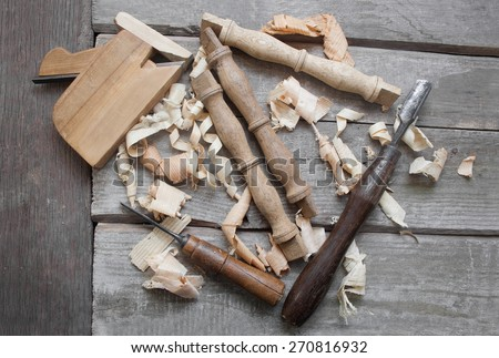 Wooden carpenter table carved elements with instruments.Wooden rusty carpenter chisels, plane lying with sawdust and carved wooden elements on rusty old table upper view. - stock photo