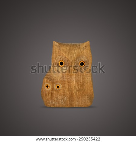 Wooden carved owls isolated on dark background  - stock photo